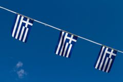 Three Greek flags on a sling, set against a blue sky. royalty free stock photo