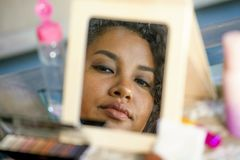 Lifestyle mirror reflection portrait of young happy and beautiful hispanic woman looking at herself after applying face makeup cos royalty free stock image