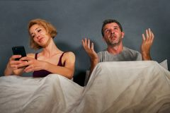 Wife using mobile phone in bed with her angry frustrated husband and the man feeling ignored upset and bored in woman internet add stock photo