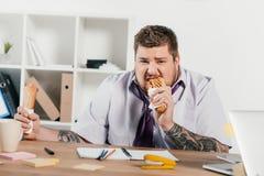 fet affärsman som äter hotdogs på arbetsplatsen Royaltyfri Fotografi