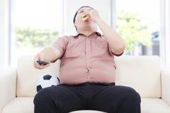 Fet affärsman som dricker öl och sitter på soffan för att hålla ögonen på TV Royaltyfri Foto