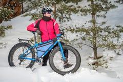 Fet cykel Fet gummihjulcykel En ung man som rider den feta cykeln i vintern royaltyfri foto