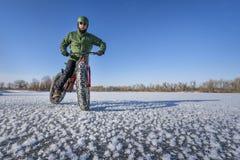 Fet cykelcyklist på en djupfryst sjö i vinter Royaltyfri Bild