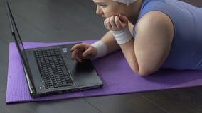 Fet flicka som framme ligger av bärbara datorn och att se SAD på skärmen, väntande på meddelande arkivfilmer