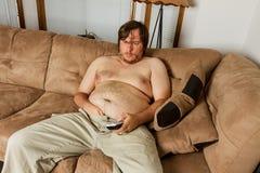 Fet grabb som lägger på soffan arkivfoto