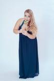 Fet kvinna i blåttklänning som äter klubban Arkivbild