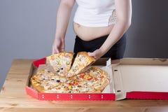Fet kvinna med ett stycke av pizza i handen, fetmabegrepp fotografering för bildbyråer