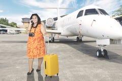 Fet kvinna med smartphonen i flygplatsen Arkivbild