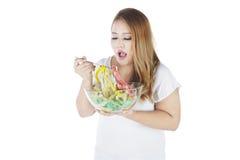 Fet kvinna som äter mäta band royaltyfria bilder