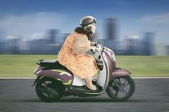 Fet kvinna som kör en motorcykel på huvudvägen Royaltyfri Fotografi