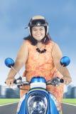 Fet kvinna som rider en sparkcykel på vägen Royaltyfria Foton