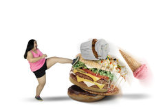 Fet kvinna som sparkar smakliga foods på studio royaltyfri bild