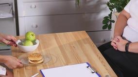 Fet kvinna som väljer mellan äpplet och hamburgaren Banta och sunt arkivbild