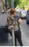 Fet kvinnabenägenhet mot en gatapol Fotografering för Bildbyråer