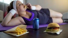 Fet lat flicka i sportswear som äter skräpmat i stället för utbildning på matt yoga royaltyfri foto