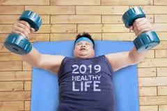 Fet man med skivstånger och 2019 sunda livtext royaltyfri foto