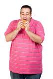 Fet man som äter en hamburgare Royaltyfria Foton