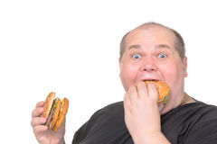 Fet man som äter Greedily hamburgaren Arkivfoton