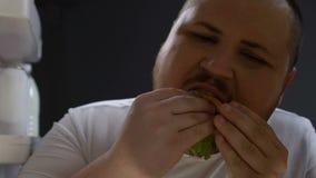Fet man som äter ivrigt hamburgaren på natten, psykologiskt matberoende, böjelse arkivfilmer