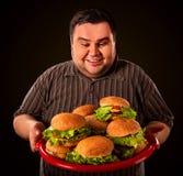 Fet man som äter snabbmathamberger Frukost för överviktig person Arkivfoto