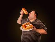 Fet man som äter snabbmatvarmkorven Frukost för överviktig person Royaltyfri Bild