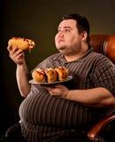 Fet man som äter snabbmatvarmkorven Frukost för överviktig person Royaltyfria Bilder