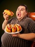 Fet man som äter snabbmatvarmkorven Frukost för överviktig person arkivfoto