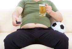 Fet man som dricker öl och sitter på soffan för att hålla ögonen på TV Royaltyfria Bilder