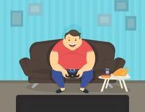 Fet man som hemma sitter på soffan som spelar videospel och att äta Arkivbild