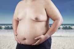 Fet man som rymmer hans mage på strand 1 arkivfoto