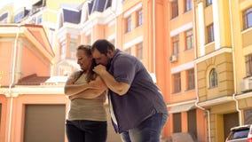 Fet pojkvän som kysser flickvännen på skuldran, lyckligt par som kramar, affektion arkivbilder