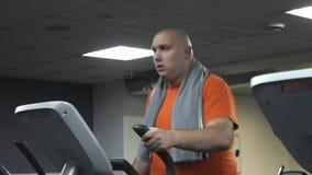 Fet rolig man med en handduk på hans skuldror som utbildar på en ellipsoid och äter hamburgaren, stock video