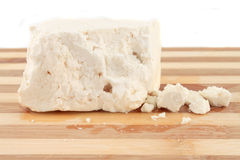 Feta cheese. Chunk of Feta Cheese with crumbles on a wooden board Royalty Free Stock Photos