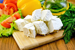 Feta cheese on the board with vegetables and salad Royalty Free Stock Photography