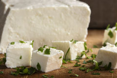 Feta cheese cubes. And parsley on a wooden background stock images