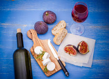 Feta cheese with ripe figs and wine on blue Royalty Free Stock Images