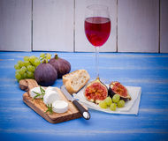 Feta cheese with ripe figs and wine on blue Stock Image