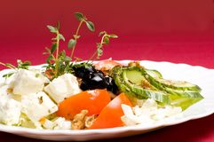 Feta-cheese salad. Healthy feta-cheese salad with fresh cucumber tomato apple and onion slices and olives over royal red background Royalty Free Stock Images