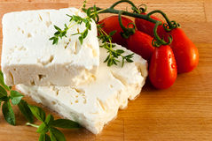 Feta cheese served with fresh tomatos, basil and thyme Stock Images
