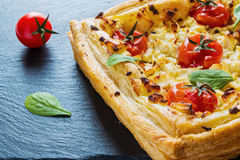 Feta cheese tart made with butter puff pastry and whole cherry tomatoes. Black stone background Royalty Free Stock Images
