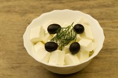 Feta cheese with traditional Greek olives on wooden background Stock Photography