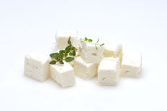 Feta cubes. Feta cheese cubes and oregano on a white background stock photo
