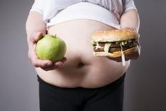 Feta kvinnor lider från fetma med den stora hamburgaren och äpplet i händer, skräpmatbegrepp royaltyfri fotografi
