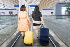Feta kvinnor som går på rulltrappaflygplatsen Arkivbilder