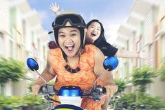 Feta kvinnor som rider en motorcykel på den bostads- gatan Arkivfoto