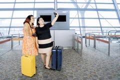 Feta kvinnor som tar ett foto i flygplatsen Royaltyfria Bilder