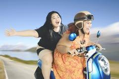 Feta kvinnor som tycker om deras semester med en sparkcykel Royaltyfria Bilder