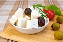 Feta with olives in cup on brown cloth and board Stock Images