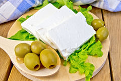 Feta with olives and lettuce on board and spoon Stock Photos