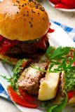 Feta stuffed turkey burgers with arugula pesto and roasted red peppers. Style rustic .selective focus Stock Photography